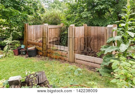 wooden compost bins in garden setting with trees