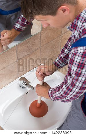 Close-up Of A Plumber Using Plunger In Bathroom Sink