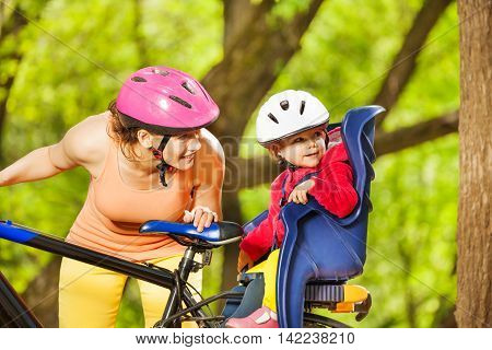 Happy mother and her little toddler daughter, sitting in bike seat with helmet, riding a bike together in the park