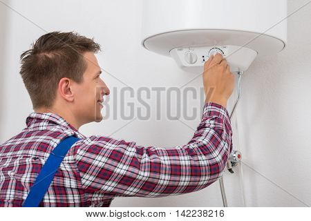Happy Young Male Plumber Turning The Knob Of Electric Boiler
