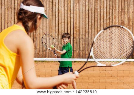 Sporty kid boy holding tennis ball and racket, starting set with his opponent on the clay court
