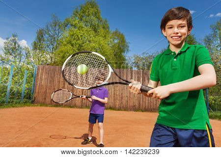 Portrait of happy tennis player, kid boy hitting forehand and his partner behind him on the tennis court