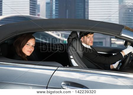 Beautiful Young Woman Traveling In A Car With Male Handsome Chauffeur