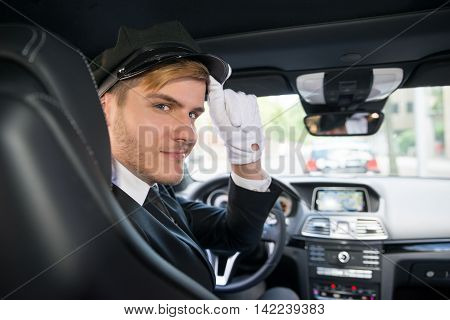 Portrait Of A Handsome Smiling Male Chauffeur Riding Car
