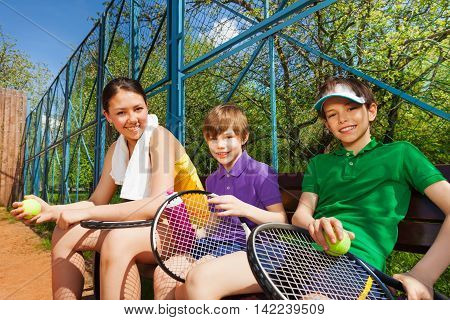 Happy smiling tennis players, teenage girl and kid boys having rest after the set, sitting on the bench, holding rackets an balls