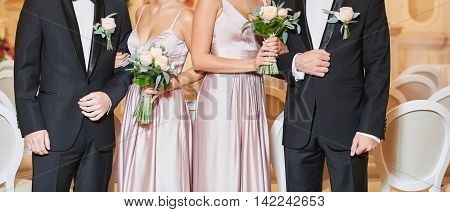 Row of bridesmaids and groomsmans with bouquets at wedding ceremony