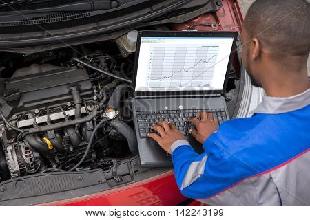 Young Male Mechanic Using Laptop While Examining Car Engine