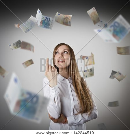 Pointing. Woman in white and falling Euro banknotes. Currency and lottery concept.