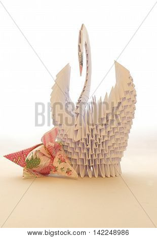 Swan made of paper for the interior, with folded napkins in the form of tulip flowers