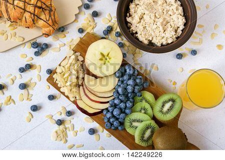 Oatmeal with kiwi, apples, almonds and blueberries. Amended orange juice in a glass, croissant and fresh fruits. A healthy breakfast on a light table, top view