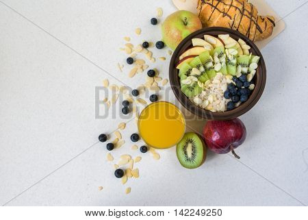 Oatmeal with kiwi, apples, almonds and blueberries. Amended orange juice in a glass, croissant and fresh fruits. A healthy breakfast on a light table, top view, copy space