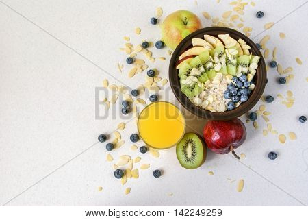 Oatmeal with kiwi, apples, almonds and blueberries. Amended orange juice in a glass and a jug. A healthy breakfast on a light table, top view, copy space