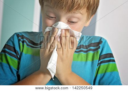An ill boy with flu blowing nose at home
