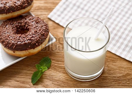 A glass of milk and glazed chocolate donuts on wooden table