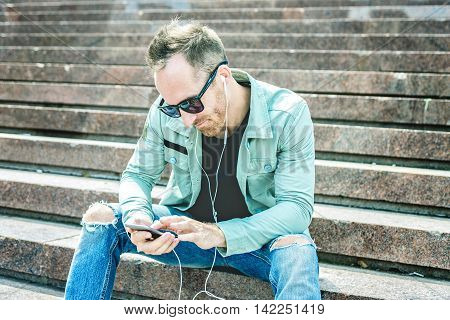 A Man listening to the music with earbuds from a smart phone