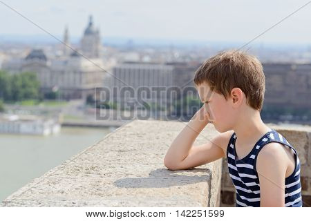 Offended sad child boy in the city center