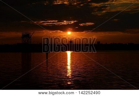 Bright sunset on the river in an industrial zone