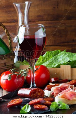 Ham Serrano and salami with bread accompanied by glass of red wine