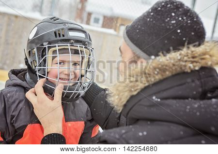 A family playing at the skating rink in winter. A father help his child to put his helmet