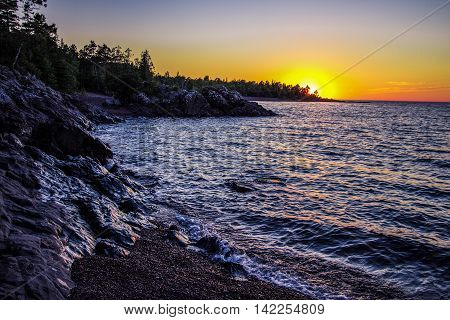 Copper Harbor Sunset. Waves crash on a remote shore of Lake Superior at the northern portion of the Keweenaw Peninsula in Copper Harbor, Michigan.