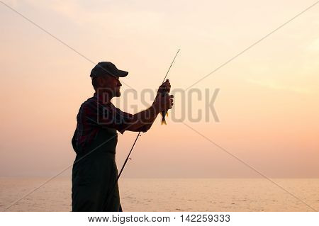 fisherman removes the fish from the hook. old man holding a fishing rod with a caught fish against the setting sun