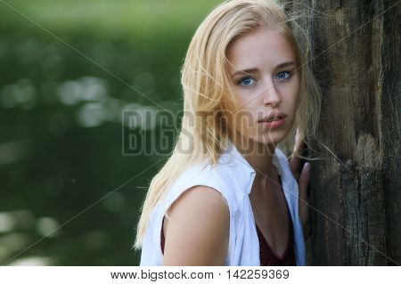 portrait of a beautiful young girl in the forest. attractive blonde girl with blue eyes leaning against the old tree. sense of foreboding