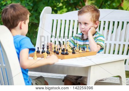 two young chess players outdoors. Children playing chess. cute young boy stares at his older rival in pending his chess move