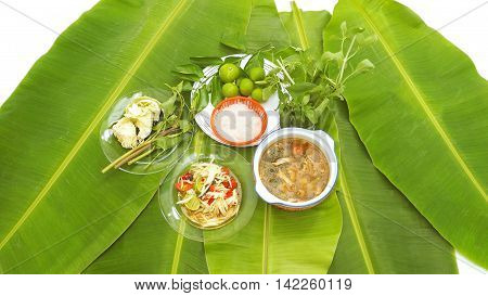 Papaya Slad and Spicy Pork Soup Thai Isan favorite herbal green food for diet control have eat with noodles vegetable lemon basil cabbageThai morning glory all on banana leaf and white background or isolate.