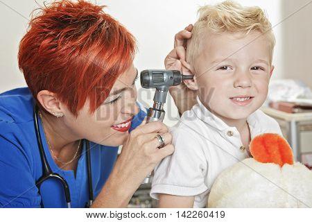A Doctor Examining the ear of a cute little boy