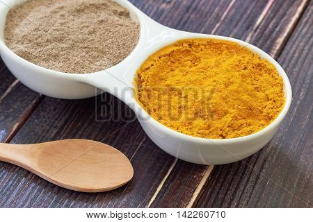 Turmeric and black pepper in white ceramic bowl on wooden background. Ingredients for golden paste. Top view with copy space