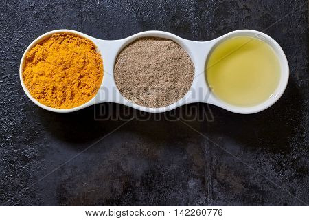 Turmeric black pepper and olive oil in white ceramic bowl on black rustic background. Ingredients for golden paste. Top view with copy space