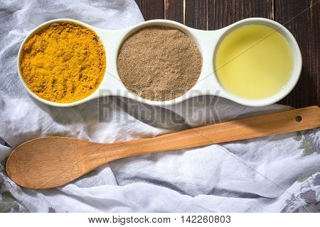 Turmeric black pepper and olive oil in white ceramic bowl on wooden background. Ingredients for golden paste poster