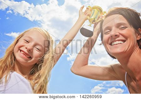 A Happy mother and daughter holding a trophy high up