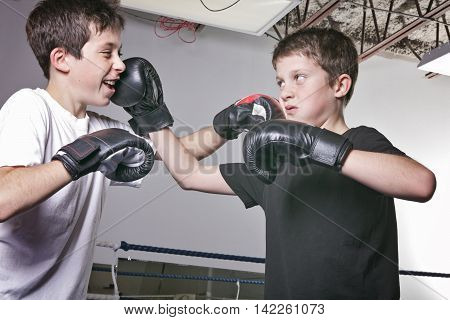 young boy with black boxing gloves fight with is brother