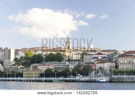 PORTUGALETE BASQUE COUNTRY SPAIN - AUGUST 11 2016: View at sunset of the town of Portugalete with the Church of Santa Maria the Salazar Tower and the Nervion river.