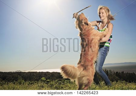A teenage girl play with is dog outside with a piece of wood.