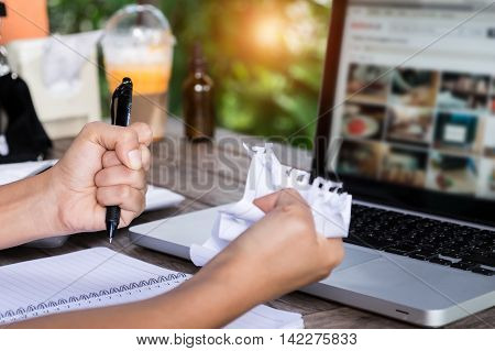 Profile of a desperate and alone business women rip a paper one wooden desk. Bankruptcy concept