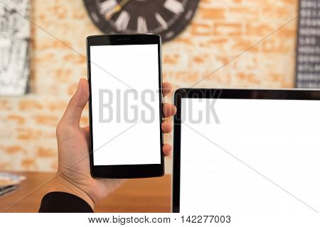 Close up of a man using smart phone with blank mobile and laptop .Smart phone with blank screen and can be add your texts or others on smart phone.