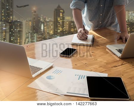 woman's hand working with business document tablet and laptop computer notebook for working concept.