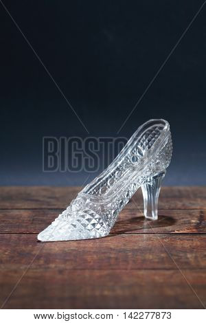 Glass slipper on old wooden board against dark background