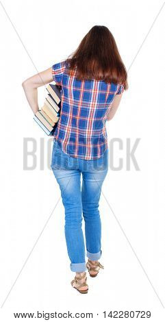 Girl comes with  stack of books. back side view. Rear view people collection.  backside view of person.  Isolated over white background. Girl in a plaid shirt goes back to us holding books under his