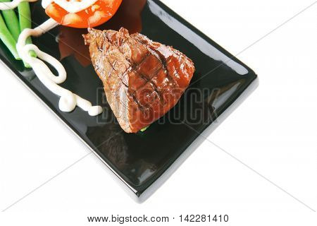 fillet mignon served on a white plate with tomato