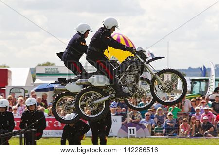 WEEDON, UK - AUGUST 29: Members of the Royal Signals White Helmets display team demonstrate a synchronised jump stunt for the public at the Bucks County show on August 29, 2013 in Weedon