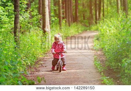 little girl riding bike in summer forest, active kids