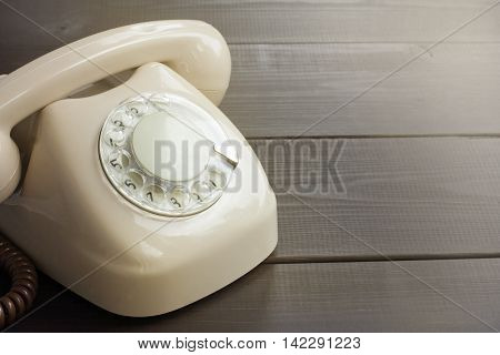Retro rotary phone beige stands on a wooden background / call waiting