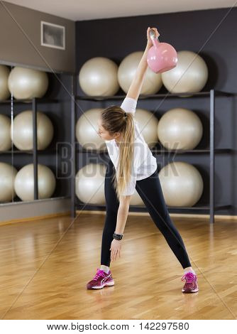 Woman Exercising While Lifting Kettlebell On Hardwood Floor At G