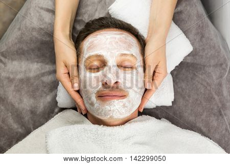 Face of man with cream mask and hands of professional cosmetologist beauty spa