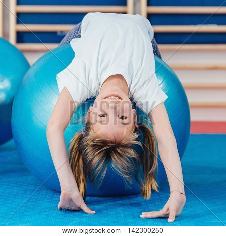 Little girl at physical education class in school gymnasium stretching over fitness ball poster