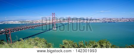 Ponte 25 de Abril across the Tagus river and view on the center of Lisbon Portugal