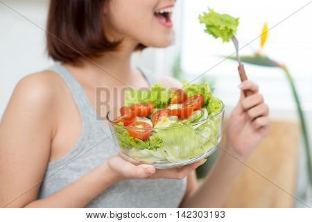 close-up of woman eating fresh salad. Beautiful young asian girl eating salad. smiling happy girl eating healthy food.